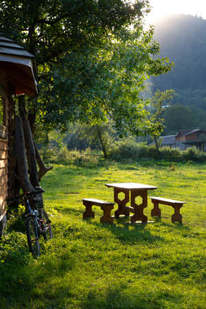 resting place with benches and table in the Carpathian mountains with the setting sun
