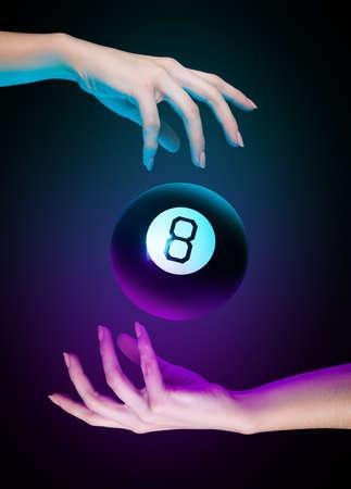 Mani con palla da biliardo magica numero otto su uno sfondo scuro. Luce ciano e viola