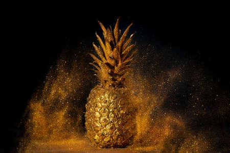 Golden pineapple. Golden metal powder flying around. Black background.
