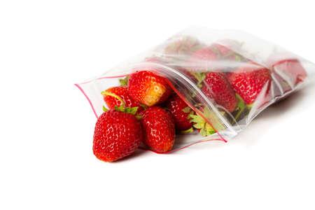 Frische Erdbeere in transparenter, offener Plastiktüte mit Schloss, isoliert auf weiss.