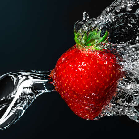 Fresh strawberry berry close-up under running water. Dark background.