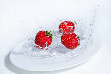 Fresh strawberries fall on a white plate. Splashes of water around the berries. White wooden table.