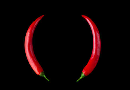 Devil horns made of red hot peppers on a black background. Imagens