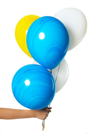 A hand is holding balloons. Isolation on white background. blue white and yellow balls. Imagens