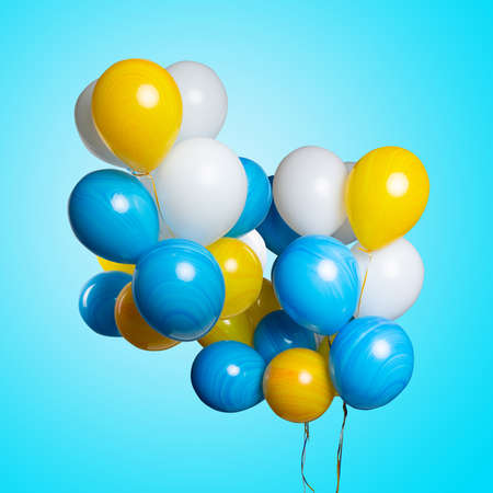 Many colorful balloons isolated on blue turquoise background. Birthday party, positive mood. Imagens