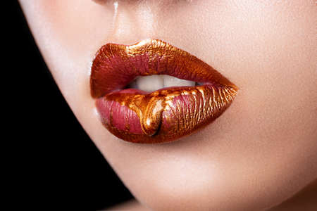 Beautiful female lips close-up. Red lipstick, red-gold paint flowing on lips. Imagens
