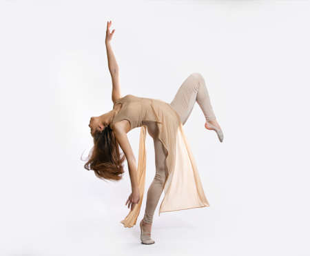 Young beautiful ballerina in a professional outfit performs a dance. Modern ballet. Girl in beautiful pose. The arm is lifted up Banco de Imagens