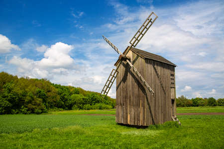 Old wooden mill on the background of beautiful nature. Imagens