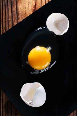 Raw broken egg and shell on black cutting Board on wooden table