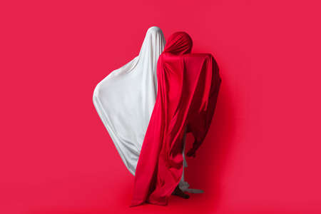 Female figures in fluttering in the wind fabrics. Red and white silhouette on a red background in the Studio. Minimalism. Concept Stock Photo