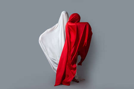Female figures in fluttering in the wind fabrics. Red and white silhouette on grey background. Minimalism. Concept