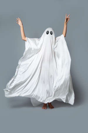 A girl in a Ghost costume on a gray background in the Studio. Halloween minimal concept. Stock Photo