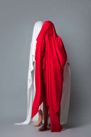 Female figures covered with a head of red and white cloth Red and white silhouette on a gray background. Minimalism. Concept Stock Photo