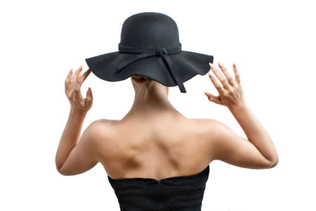 girl in a black hat posing standing back. white background, hands holding the edge of the hat Archivio Fotografico