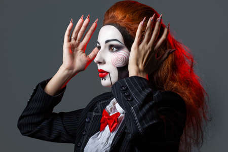 Red-haired girl with creative make-up and hairstyle for a Halloween party. Hands raised. the image of a scary doll Reklamní fotografie