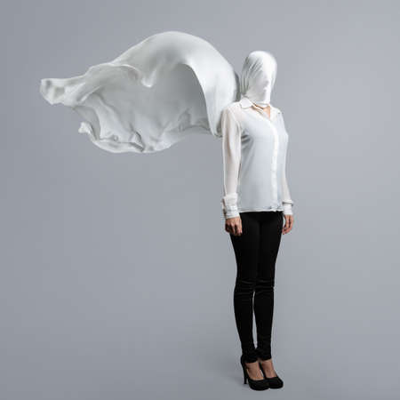 Anonymous model, covered with a white cloth. A woman in a white shirt and dark pants with her head wrapped in a waving white veil on a light gray background
