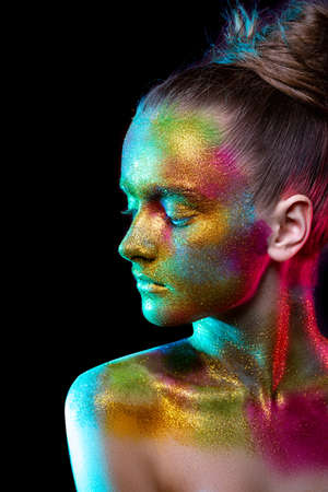 Beautiful girl in colorful bright sequins and colorful lights posing in the Studio . Art design colorful bright makeup