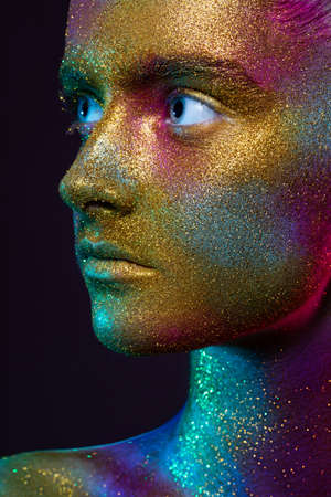 Beautiful model with creative make-up. gold, yellow, blue, purple and green paint on the skin, space and stars. Metal powder, glitter. Face close-up