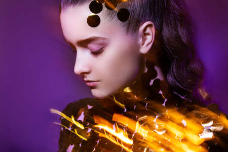creative portrait of a young girl. bright streaks of light are reflected in the sequins. Shooting at a large exposure. purple background Reklamní fotografie