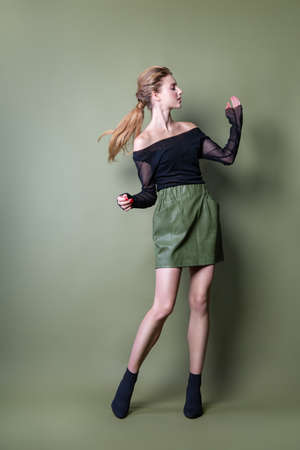 young beautiful woman in a black jacket and green skirt posing in the Studio. Attractive female model in stylish casual clothes on green background