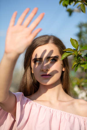 young woman covered her face from the sun with her hand outdoors. Reklamní fotografie