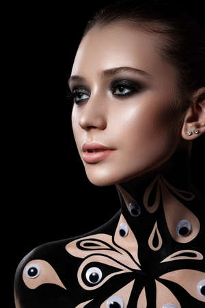 Beautiful girl with a professional evening make-up. neck and shoulders are painted with black paint. Perfect skin. body painting
