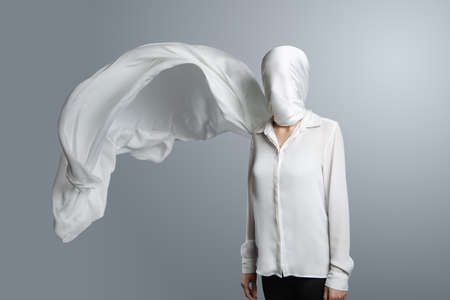 Anonymous model, covered with a white cloth. Woman in white shirt with head wrapped in waving white veil on light grey background