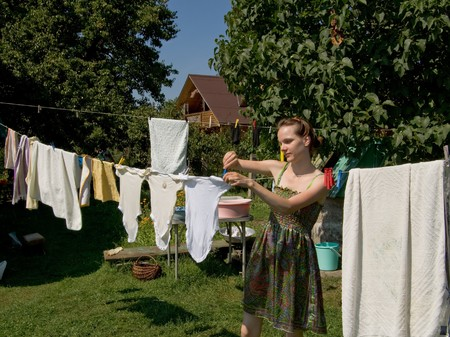 She hangs up the clean clothes on a rope in the garden Stock Photo