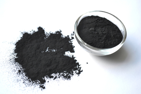 Powdered activated charcoal in a glass jar. Natural ingredient for beauty treatments, skin care, detox face masks, dental care. Foto de archivo