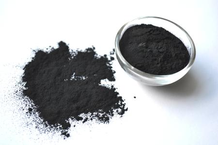 Pulverisierte Aktivkohle in einem Glasgefäß. Natürlicher Inhaltsstoff für Schönheitsanwendungen, Hautpflege, Detox-Gesichtsmasken, Zahnpflege. Standard-Bild - 87744277
