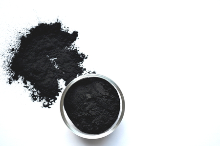Powdered activated charcoal in a glass jar. Natural ingredient for beauty treatments, skin care, detox face masks, dental care. Archivio Fotografico