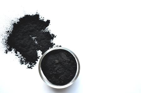 Pulverisierte Aktivkohle in einem Glasgefäß. Natürlicher Inhaltsstoff für Schönheitsanwendungen, Hautpflege, Detox-Gesichtsmasken, Zahnpflege. Standard-Bild
