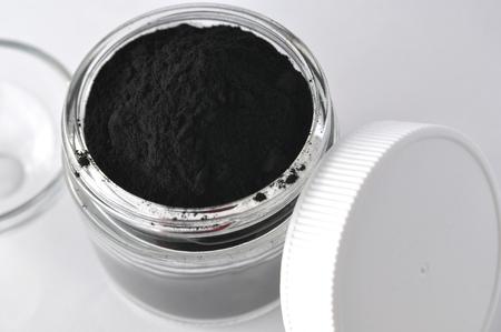 Actieve actieve kool in een glazen pot. Natuurlijk ingrediënt voor schoonheidsbehandelingen, huidverzorging, detox gezichtsmaskers, tandheelkundige zorg. Stockfoto - 87569463