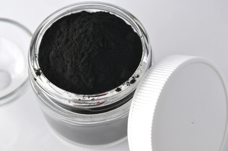 Powdered activated charcoal in a glass jar. Natural ingredient for beauty treatments, skin care, detox face masks, dental care. Stock Photo