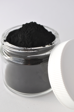 Powdered activated charcoal in a glass jar. Natural ingredient for beauty treatments, skin care, detox face masks, dental care. Stock fotó