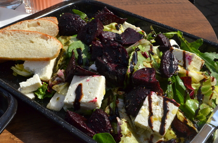 Grilled red beet salad with feta cheese on a bed of mixed greens