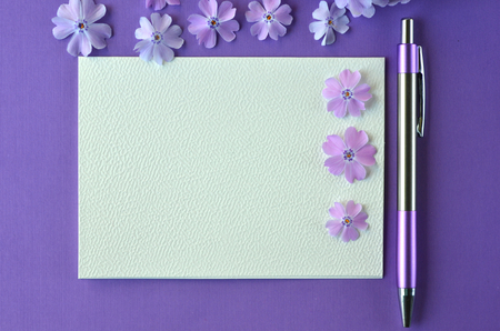 Ultra violet flatlay of feminine stationery, notebook, pen, lavender phlox flowers with copy space. Brainstorming ideas, note taking or diary writing concept. Background for invitations and messages.
