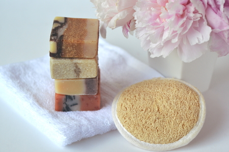 Luxury beauty Spa skincare, serum and creams with pink peonies and natural handmade soap bars with loofah massage mitten