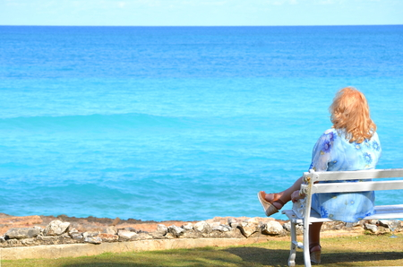 Senior plus size blond woman sitting on a bench looking at the blue ocean with copy space. Solo vacation on a tropical island, travel, leisure and self-care theme. 免版税图像