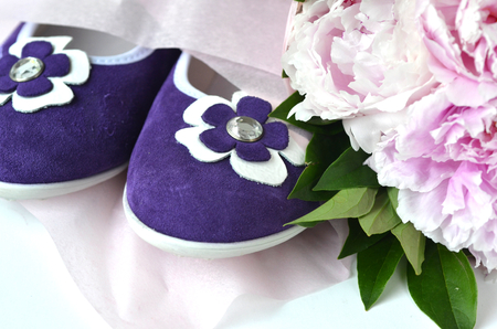 Purple violet suede leather ballerina flats shoes with blush pink peonies bouquet wrapped in a tissue paper with copy space