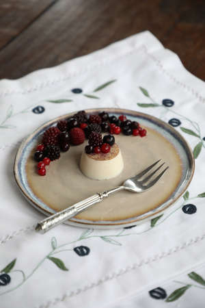 Panna Cota dessert with berries on a large plate with a white tablecloth background for the inscription