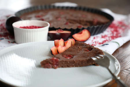 chocolate cake with cherries raspberries and plums on a dark table with a light tablecloth