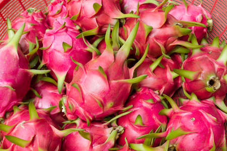 Lots of dragon fruit in red basket  photo