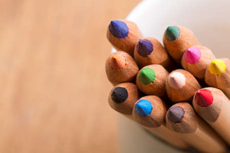 colored pencils with brown blurred background photo
