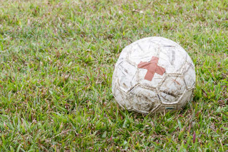 patched: old football with patched on field Stock Photo