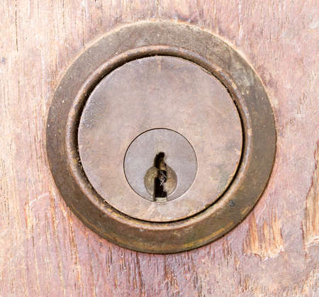 door lock: rounded aged keyhole on wooden wall - closed up