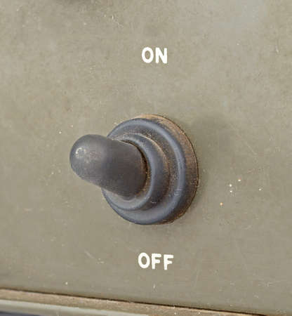 toggle switch: closed up old black toggle switch on green surface - on Stock Photo