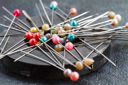 attach: Pins attach round magnetic pincushion on black leather background