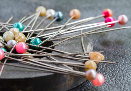 Pins attach round magnetic pincushion on black leather background