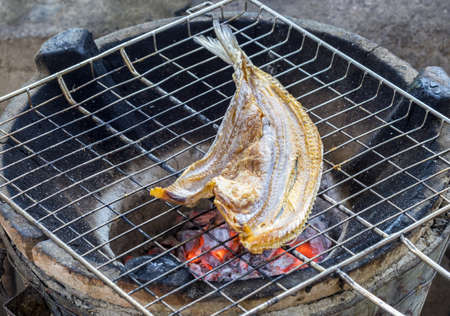 Grilled dried snake-head fish on hot red charcoal Stock Photo